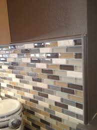 glass mosaic backsplash in neutral colors complete with schluter edge profile pieces