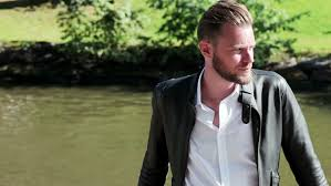 a man wearing a black leather jacket and white shirt relaxing outside with the river behind him on a sunny summer day