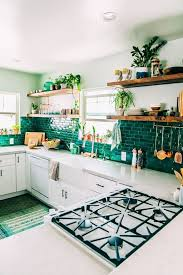 emerald rectangular tile backsplash white kitchen cabinets white countertops wooden floating shelves potted plants plates cups napkins