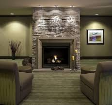 interior brown stone fireplace mantel with yellow candles on the black stand beside captivating