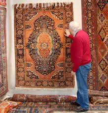 oriental rugs oriental textiles at arts east show in boston wiscasset maine antiques dealer michael dunn looks at a rug in doug stock s booth