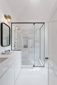 large glass wall shower + black trim, patterned tile, brass hardware, all  white