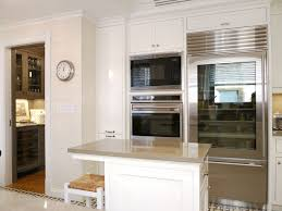 richard mervis high rise kitchen with glossy white cabinets and kitchen island with lagos azul limestone countertops glass front fridge next to double