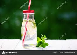 refreshing homemade flavored water with lemon lime and mentha on a white table in garden