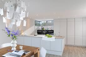 moderne Inselküche mit Betonarbeitsplatte und weißen Fronten