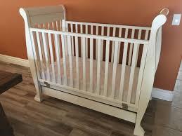 white wooden crib with mattress mattress pad and storage drawer