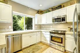 White Kitchen With Hardwood Floors White Kitchen Cabinets With Steel Appliances And Light Tone