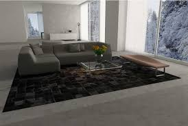 big brown and black patchwork cowhide rug under a gray cough in a big living room