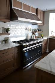 chic kitchen features maple cabinets paired with statuary marble countertops and a white linear brick tile backsplash