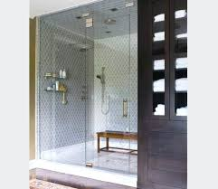 walk in shower with gray glass tiles and glass fold down