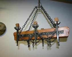 antique chandelier with brown stained oak wood based and black wrought iron candle cup also hanger