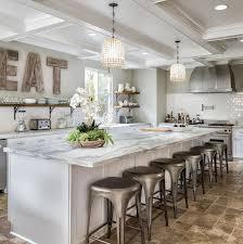 Kitchen features a long island with white and gray marble countertop.  Kitchen with long island