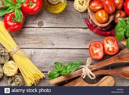 kitchen table with food. Italian Food Cooking. Tomatoes, Basil, Spaghetti Pasta, Olive Oil And Chili Pepper On Wooden Kitchen Table. Top View With Copy S Table O