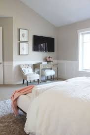 gorgeous bedroom features beige paint on upper walls and wainscoting on lower walls framing flatscreen tv