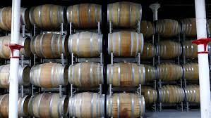 stacked oak wine barrels. Wine Production And Bottling Area In Cellar Featuring Transport Rows Of Oak Barrels After Vintage Harvest. Barossa Valley, Clare Stacked O