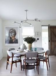 modern dining room with round dining table gray upholstered dining chairs and a modern globe