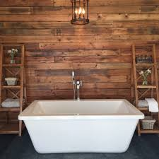 stand alone tub right in the middle of the image set against a wooden wall