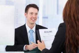 Young Man Handing Resume to Woman Interviewer