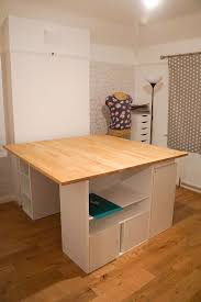 picture of diy huge sewing table for a craft room custom storage shelving unit