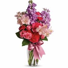 a small vase with pink and purple flowers jumping for joy bouquet