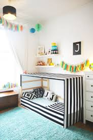 An IKEA Kura bed hack in a child's room featuring a black and white striped  fabric