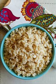 instant pot brown rice p1 turquoise bowl with brown rice with flowered napkin in background
