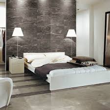 Dark silver marble effect tiles have been used on the wall of this modern  bedroom and