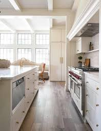 An Off White Kitchen Island Is Fitted With Plank Drawers And A Microwave  Alongside A Prep Sink.