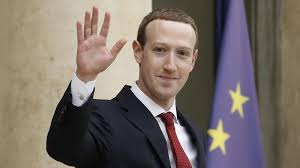 ceo and co founder of facebook mark zuckerberg waves at journalists as he leaves the elysee palace after his meeting with french president emmanuel macron