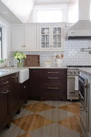 amazing kitchen features light grey upper cabinets and dark brown lower cabinets paired with gray granite countertops and a white subway tiled backsplash