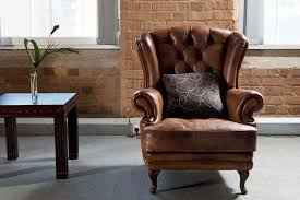 furniture brown leather side chair with arm and tufted back rest plus square wooden table placed grey carpet combined brick wall well chairs living room for
