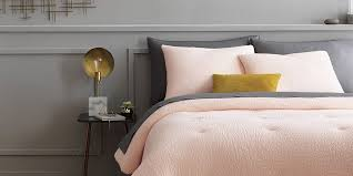 a bed with dark grey and pale pink bedding finished with a yellow throw pillow