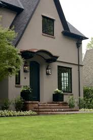 tudor stucco home with taupe paint and black roof and trim