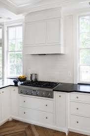 white kitchen cabinets with brass hardware and black countertops