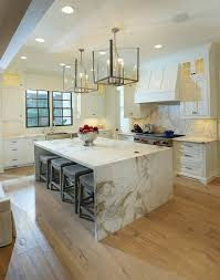 stunning kitchen features glass and nickel lanterns illuminating marble waterfall island lined with gray backless barstools