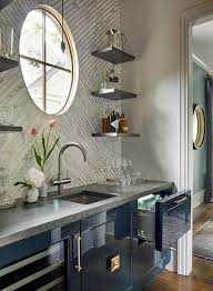 glossy blue kitchen bar cabinets with gray wood countertops and white and gold chevron backsplash