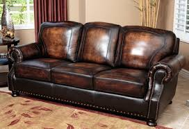 The rich burnt tone of this luxurious leather sofa enhances the sense of  traditional charm. Roll arms and base feature nailhead trim, while the  carefully ...