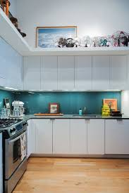 Back painted glass panels add a pop of teal to this loft kitchen in New  Jersey.