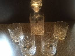 a cut crystal whiskey decanter with four cut crystal whiskey glasses