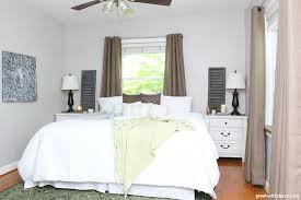 a gray bedroom with white bedding brown curtains a green rug and green blanket