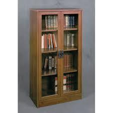 high brown wooden bookshelf with double glass doors having black metal handles