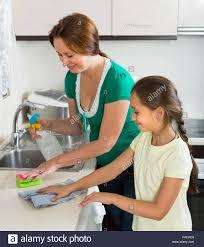 dusting furniture. Smiling Schoolgirl Helping Mother Dusting Furniture Indoor. Focus On Girl E