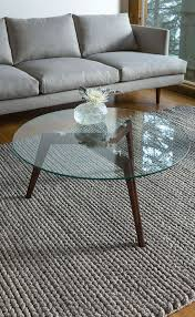 mid century modern coffee table with dark stained wooden legs and a round glass top