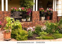 Beautiful garden with flower box and pot plants on the porch
