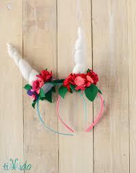 two felt unicorn horn headbands with felt flowers on a whitewashed wood background