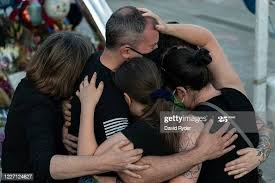 Family members embrace Police Officer Chris Rigler next to a ...
