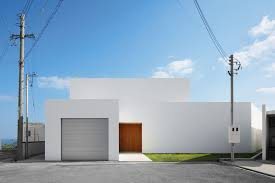 This simple white minimalist house features a grey garage door and a wood  front door to give the house a modern look and warm up the all white  exterior.