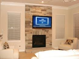 black wall mount tv on beige stone wall over black fireplace added by ivory sofa set and white ceiling fan in white livingroom
