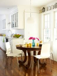 an all white traditional kitchen is brightened up with this beautiful little breakfast nook i love the contrast between the sleek lines of the white chairs