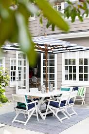 white x based outdoor dining table and white folding chairs